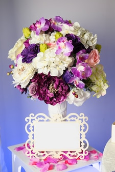Background with colorful flowers in vase, and empty tag for text