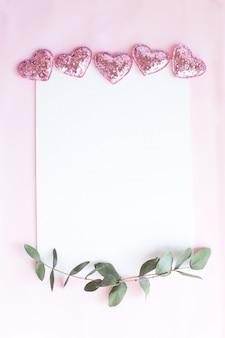 ピンクのキラキラハート、ユーカリの枝とピンクの背景にコピースペース空白の背景。ホワイトペーパーの上面図、フラットレイ、最小限のスタイル。カードをモークアップします。