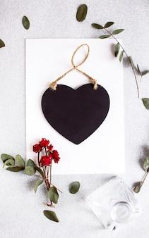 黒いハート、ユーカリの枝、バラの花と葉とテーブルの上のコピースペース空白の背景。ホワイトペーパーの上面図、フラットレイ、最小限のスタイル。カードをモークアップします。