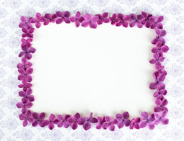 라일락 보라색 꽃이 있는 테이블에 빈 복사 공간이 있는 배경. 보라색 꽃입니다. 백서 상단 보기, 평평한 평지, 최소한의 스타일. 모크 업 카드.