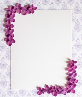 ライラック紫の花とテーブルの上のコピースペース空白の背景。紫の花。ホワイトペーパーの上面図、フラットレイ、最小限のスタイル。カードをモークアップします。