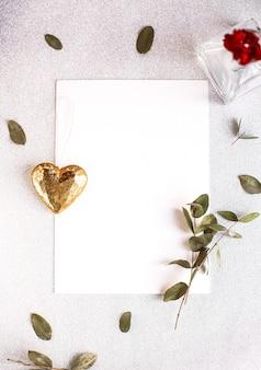 キラキラハート、ユーカリの枝、花と葉と白いテーブルの上のコピースペース空白の背景。ホワイトペーパーの上面図、フラットレイ、最小限のスタイル。カードをモークアップします。
