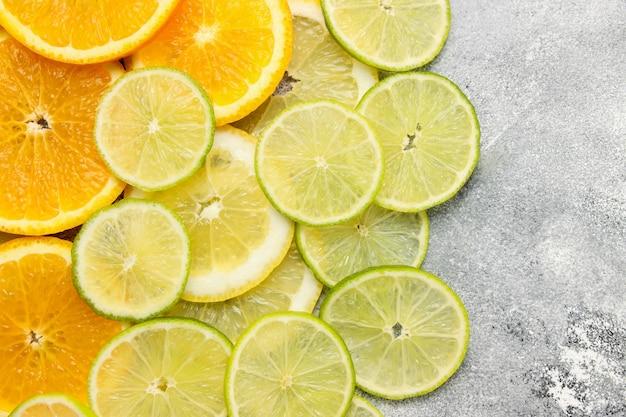 Фон с нарезанными цитрусовыми фруктами круглой формы, нарезанными апельсинами, лаймами и лимонами