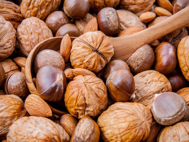 Background with different kinds of nuts with wooden spoon.