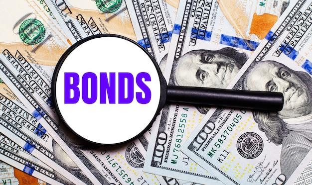 Фон с долларовыми купюрами под увеличительным стеклом с текстом облигации. финансовая концепция