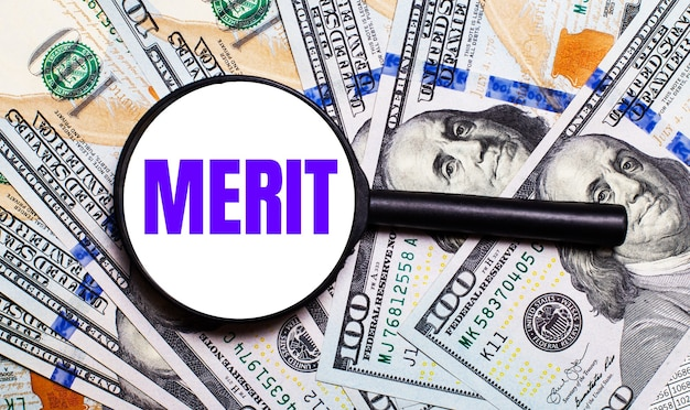 テキストmerit.financialconceptの拡大鏡の下でのドル紙幣の背景