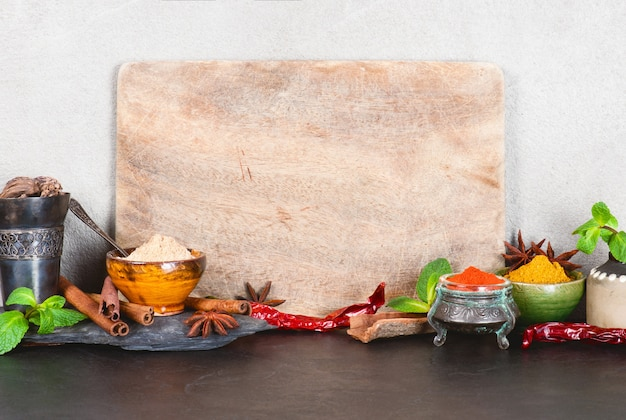 Background with empty cutting board and various oriental spices