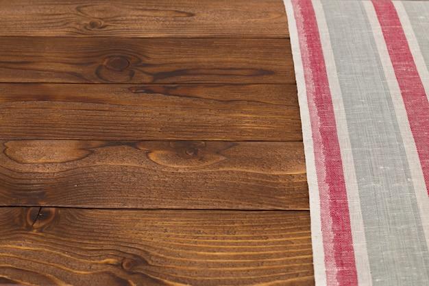 Фон с пустым деревянным столом со скатертью