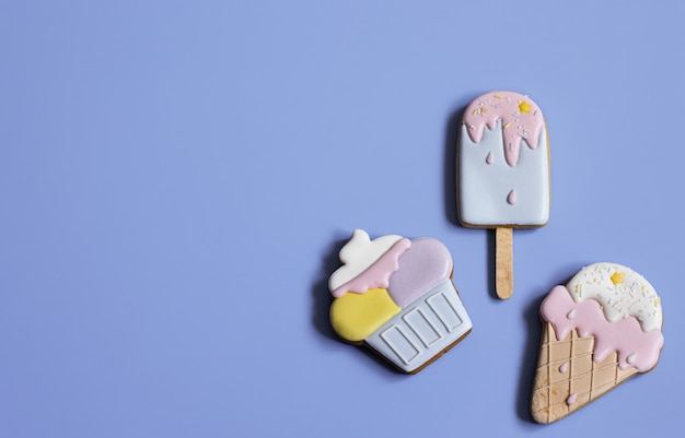 Background with festive gingerbread cookies in the form of sweets, covered with glaze copy space.