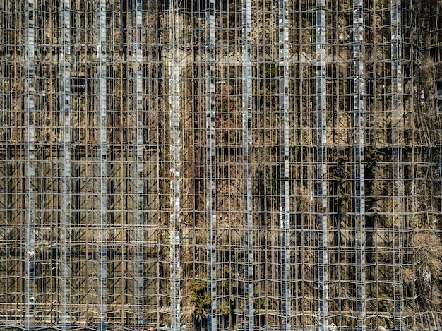 Background with framework of metal constructions greenhouses bird's eye view from drone.