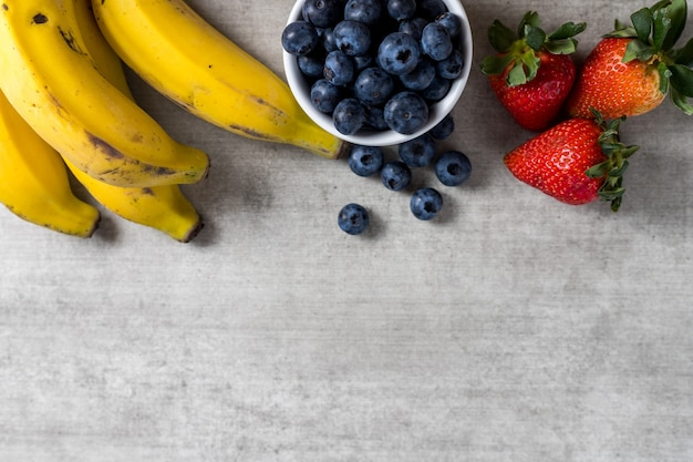 Фон со свежими здоровыми фруктами на деревянном столе. бананы, черника и клубника. вид сверху. скопируйте пространство.