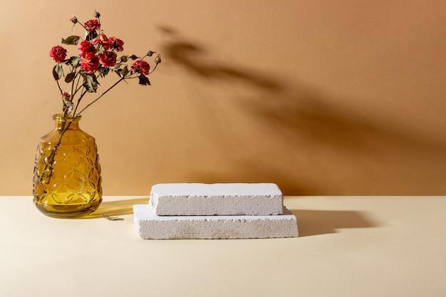 화장품용 콘크리트로 만들어진 기하학적 모양이 있는 배경. 직사각형 연단, 말린 꽃과 베이지색 배경에 그림자가 있는 유리 꽃병. 제품에 대한 빈 모형