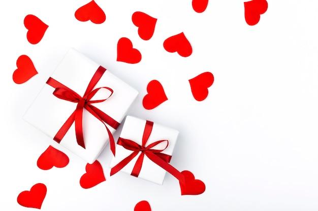 白い背景のテキストのコピースペースとギフトとハートの背景。フラットレイ、上面図。バレンタインデーのコンセプト。母の日のコンセプト。