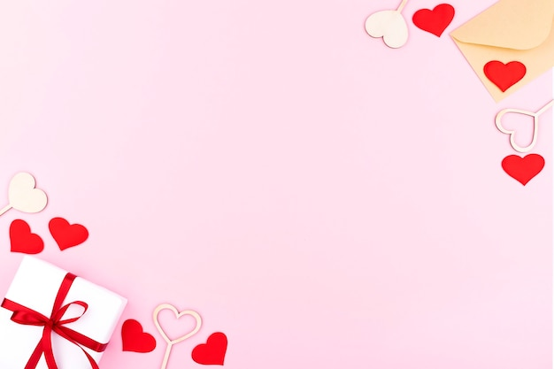 Background with gifts, envelope, hearts with free space for text on pastel pink background. flat lay, top view. valentines day concept. mother's day concept.