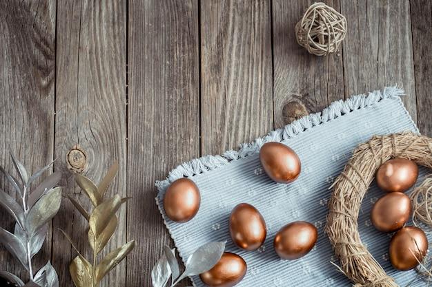 Фон с золотыми пасхальными яйцами на деревянных фоне.