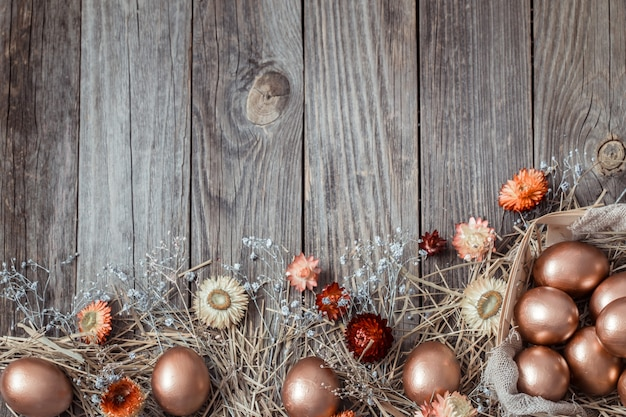 Background with golden easter eggs on wooden background.