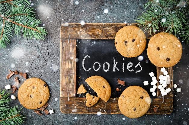 自家製チョコレートチップクッキーとマシュマロの背景。クリスマスフードフレーム。