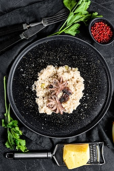 Background with homemade risotto, octopus, mushrooms, parsley, shallots, parmesan and spices. top view
