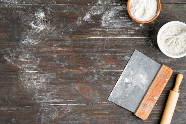 Background with ingredients for preparing fresh homemade dough on brown wooden background.