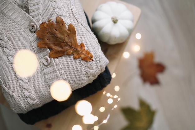 Фон с вязаной одеждой и осенними листьями концепция осень-зима