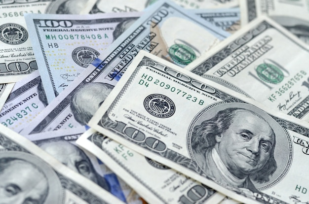 Background with many hundred dollar bills close up