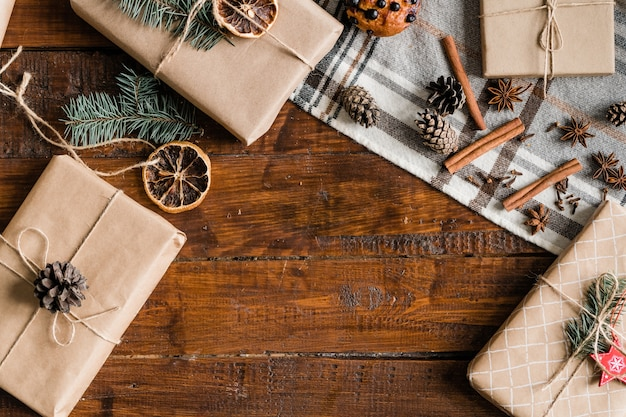 Background with packed and wrapped boxes with christmas gifts, pinecones, decorations and spices on wooden table