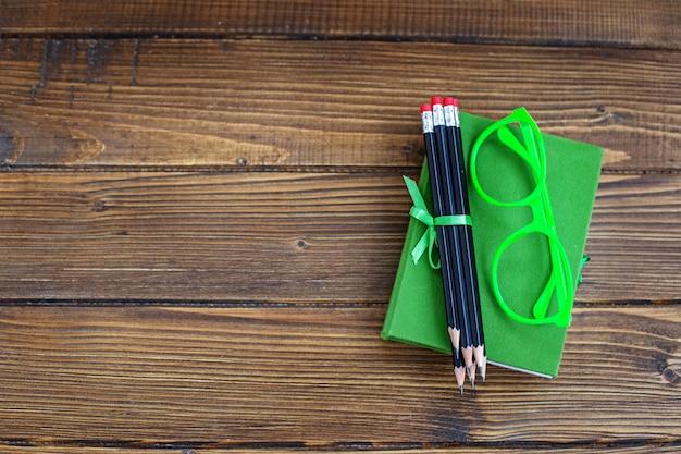 Фон с карандашами и очки и книга. вид сверху.
