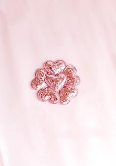 ピンクのキラキラハートの背景。ピンクの紙の上面図、フラットレイ、最小限のスタイル。カードをモークアップします。