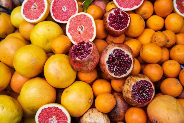 Background with raw fresh fruit - orange, tangerine, lemon, pomegranate and grapefruit.