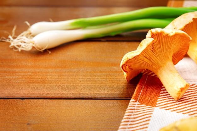 Фон с сырцовыми золотыми грибами лисичек. сезонные грибы, урожай на деревянном столе с клетчатой салфеткой и зеленым луком. крупным планом, макрос. ингредиент для гастрономического меню ресторана