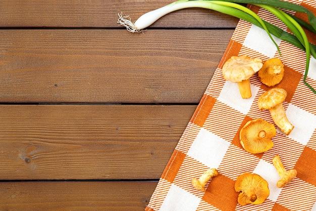 Фон с сырцовыми золотыми грибами лисичек. сезонные грибы, урожай на деревянном столе с клетчатой салфеткой и зеленым луком. пустое место для текста. плоская планировка, вид сверху.