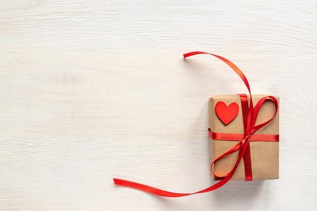 Предпосылка с красными сердцами и подарочной коробкой корабля на белом деревянном столе. концепция дня святого валентина. плоская планировка, вид сверху.