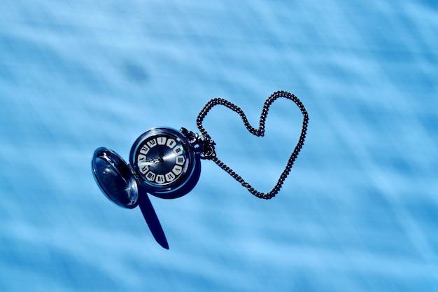 レトロな懐中時計とハードライトと青い表面にチェーンから作られたハートの背景