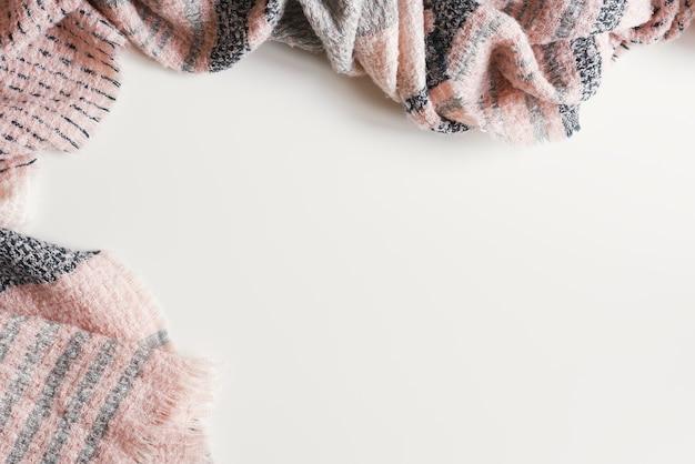 Фон с шарфом розового цвета, вид сверху, место для текста. зимний сезон