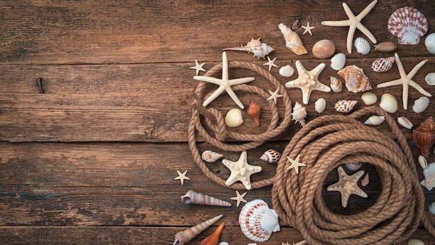 Фон с ракушками, морскими звездами и веревкой на коричневом деревянном фоне.