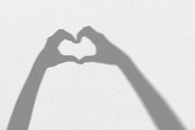 심장 기호를 만드는 손의 그림자와 배경