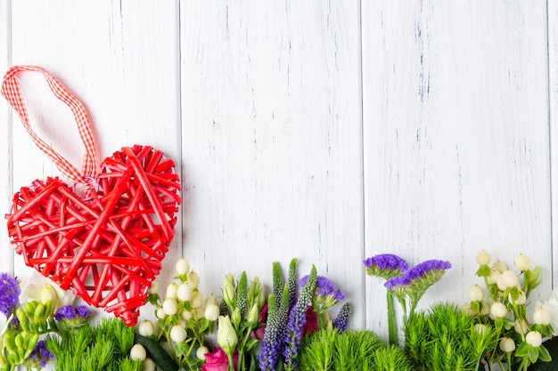Background with spring flowers and decoratiove wooden heart