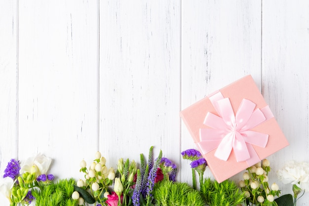 Background with spring flowers and pink gift box