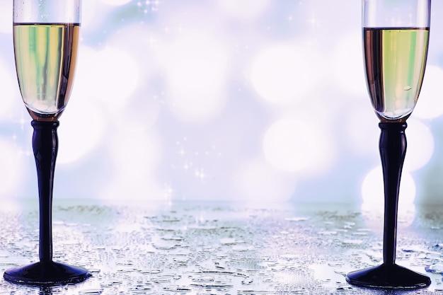 スパークリングワイン用の背の高いグラスの背景。ガラスグラスにシャンパンとスプレー。振り返りのあるお祝いドリンク。