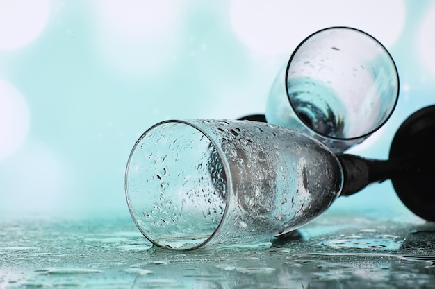 스파클링 와인을 위한 키가 큰 안경이 있는 배경. 유리잔에 샴페인과 스프레이. 반사와 기념 음료입니다.