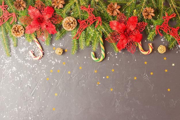 전통적인 크리스마스 장식이 있는 배경 - 붉은 꽃, 사슴, 카라멜 지팡이. 가문비나무 가지와 콘이 있는 검정색 배경. 복사 공간입니다.