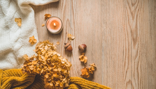 Background with warm sweaters and cup tea. cozy still life in warm shades. autumn winter concept.