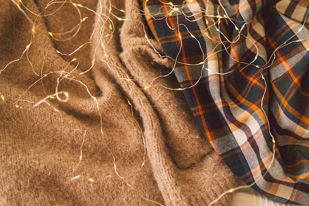 Background with warm sweaters and gerland knitted clothes space for text autumn concept