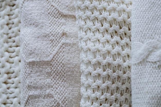 暖かいセーターの背景。暖かい色合いのニット服の山
