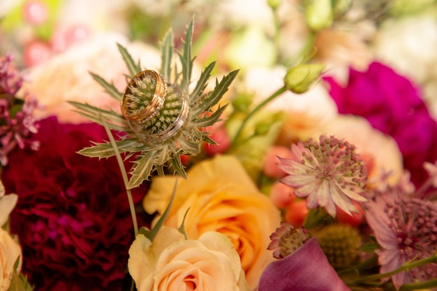 Background with wedding rings in flowers bouquets marriage