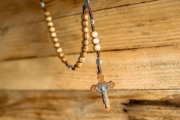 木製の十字架とキリスト教の宗教的な数珠の背景