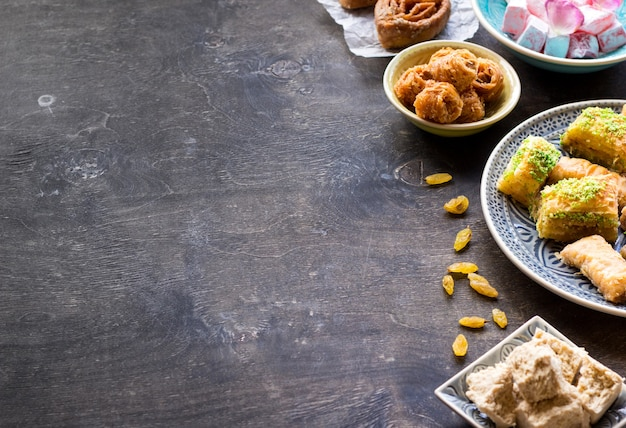 Background witn assorted traditional eastern desserts. different arabian sweets on wooden table.