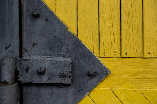 배경 검은 문 경첩으로 나무 질감입니다. 오래 된 노란색 페인트 널빤지. 오래 된 나무로되는 문에 경첩의 세부 사항