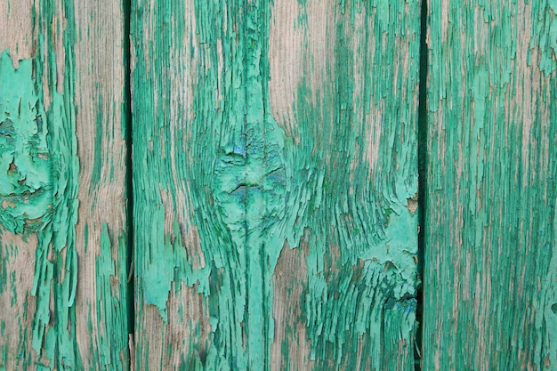 The background of wooden boards painted green peeling paint.