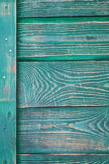 Background of wooden textured boards with a vertical plank with traces of green paint.